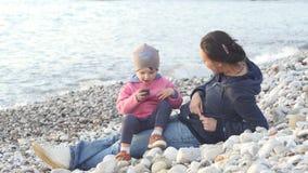 Modern och barnet sitter på stranden och tycker om solnedgången lager videofilmer