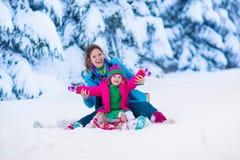 Modern och barnet som sledding i ett snöig, parkerar Arkivbild