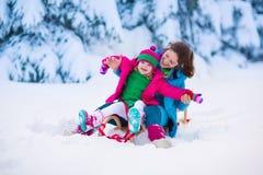 Modern och barnet som sledding i ett snöig, parkerar Fotografering för Bildbyråer