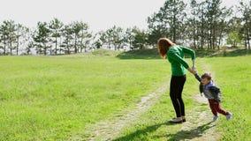 Modern och barnsonen går på vägen i skogen stock video