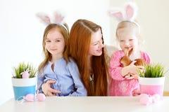 Modern och döttrar som bär kaninen, gå i ax på påsk Fotografering för Bildbyråer