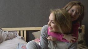 Modern och den lilla dottern är spela och krama på sängen lycklig motherhood lager videofilmer
