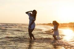 Modern och den lilla dottern har gyckel på stranden Fotografering för Bildbyråer