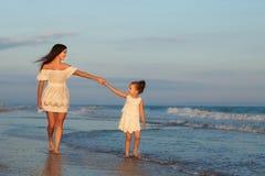 Modern och den lilla dottern har gyckel på stranden Royaltyfria Bilder