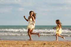 Modern och den lilla dottern har gyckel på stranden Royaltyfri Foto