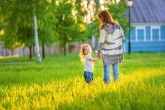 Modern och den lilla dottern i den soliga våren parkerar royaltyfri bild