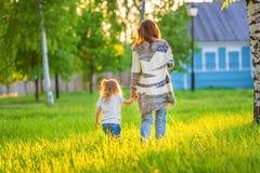 Modern och den lilla dottern i den soliga våren parkerar royaltyfria foton
