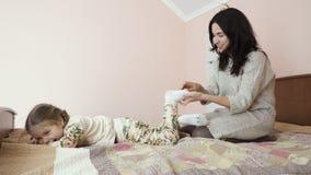 Modern och den lilla dottern kopplar av på sängen hemma stock video