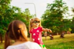 Modern och den lilla dottern som tillsammans spelar i, parkerar Utomhus- stående av den lyckliga familjen Lycklig glädje för dag  arkivbild