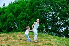Modern och den lyckliga sonen som spelar i sommar, parkerar fotografering för bildbyråer