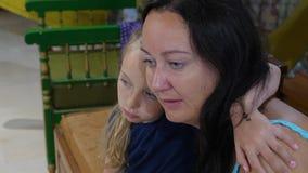 Modern och den tonåriga dottern kramar tätt upp Omfamna för mamma och för dotter lager videofilmer