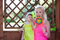 Modern och dottern äter söta godisar Royaltyfri Bild
