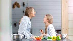 Modern och dottern bedrar omkring och spelar i ett kök stock video