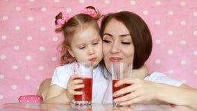 Modern och dottern dricker smoothies som ler Ung kvinna med hennes barn som tycker om en uppfriskande smaklig drink Rosa färger arkivfilmer