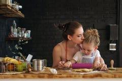 Modern och dottern förbereder kakor i kök Arkivfoton