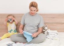 Modern och dottern förbereder tillsammans kläder för en nyfödd pojke royaltyfria foton