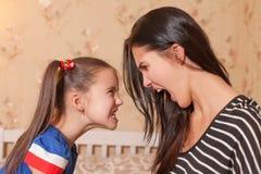 Modern och dottern gör sig ruskiga framsidor Royaltyfri Bild