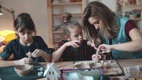 Modern och dottern göt entusiastiskt från lera i krukmakerit arkivfilmer
