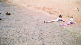 Modern och dottern har en vila, kopplar av i havet i kläder arkivfilmer