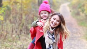 Modern och dottern har gyckel i höstskogen på en gå stock video