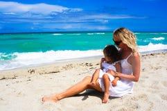 Modern och dottern har gyckel på stranden Arkivbild