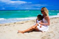 Modern och dottern har gyckel på stranden Fotografering för Bildbyråer