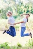 Modern och dottern hoppade floden Royaltyfri Foto