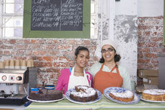 Modern och dottern i förkläden som står på kakan, shoppar räknaren arkivbilder