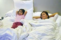 Modern och dottern kopplar av i säng som tycker om en TV-program arkivbild