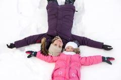 Modern och dottern lägger på snön royaltyfria bilder