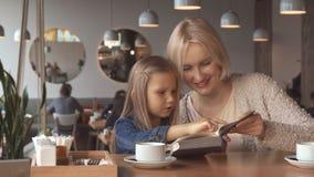 Modern och dottern läste boken på kafét royaltyfri foto