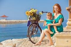 Modern och dottern med cykeln på havet sätter på land Royaltyfria Bilder