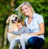 Modern och dottern med husdjuret är på gräset royaltyfria bilder