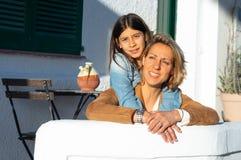 Modern och dottern omfamnade i solnedgång i en medelhavs- by med vita väggar arkivfoton