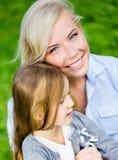 Modern och dottern omfamnar sig på gräset Royaltyfria Bilder