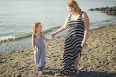 Modern och dottern på stranden sid ha gyckel Arkivfoto