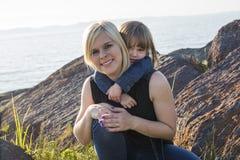 Modern och dottern på stranden sid ha gyckel Royaltyfri Foto