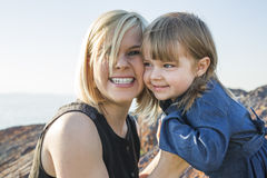 Modern och dottern på stranden sid ha gyckel Fotografering för Bildbyråer