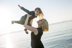 Modern och dottern på stranden sid ha gyckel Royaltyfri Fotografi