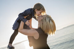 Modern och dottern på stranden sid ha gyckel Arkivbild