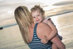 Modern och dottern på stranden sid ha gyckel Arkivfoton