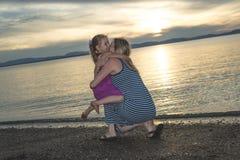 Modern och dottern på stranden sid ha gyckel Royaltyfri Bild