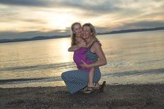 Modern och dottern på stranden sid ha gyckel Arkivbilder
