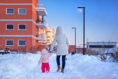 Modern och dottern på vinter går Arkivfoton