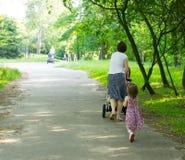 Modern och dottern parkerar går Arkivfoto