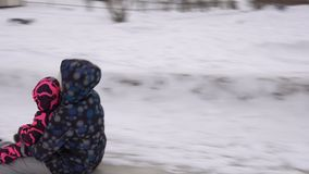 Modern och dottern rider tillsammans på en iskulle på en vinterdag lager videofilmer