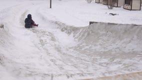 Modern och dottern rider tillsammans på en iskulle på en vinterdag arkivfilmer