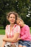 Modern och dottern sitter i park Arkivbilder