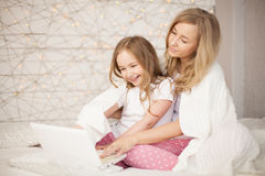 Modern och dottern sitter på säng i pyjamas och har gyckel, använder bärbara datorn livsstil lycklig familj Utbildning lär fotografering för bildbyråer