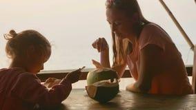 Modern och dottern sitter på seaviewkafét med kokosnötter fotografering för bildbyråer